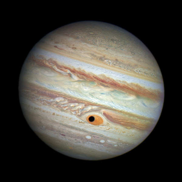 This NASA/ESA Hubble Space Telescope image shows a gorgeous close-up view of the planet Jupiter. Astronomers were using Hubble to monitor changes in Jupiter's immense Great Red Spot (GRS) storm. During the exposures, on 21 April 2014, the shadow of the Jovian moon Ganymede swept across the center of the GRS. Giving the giant planet the uncanny appearance of having a pupil in the center of a 16 000 kilometre wide eye.